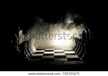 Photo of  Chess board game concept of business ideas and competition and strategy ideas concep. Chess figures on a dark background with smoke and fog. Selective focus