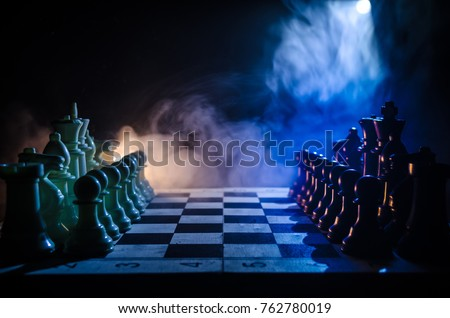 Stock Photo Chess board game concept of business ideas and competition and strategy ideas concep. Chess figures on a dark background with smoke and fog. Selective focus