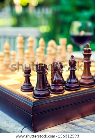 Chess board game with a glass of wine on a wooden table in a french vineyard during summer time