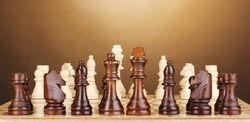 Chess board with chess pieces on brown background