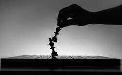 Chess board with chess pieces silhouettes on white background. Concept of business ideas, competition and strategy ideas. Black and White classic art photo. Chess player hand. Weak king was defeated