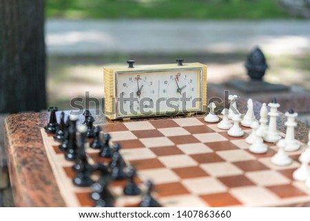 Chess board with pieces and clock on wooden desk In connection with the chess tournament. Chess tournament with chess clock on wooden table #1407863660