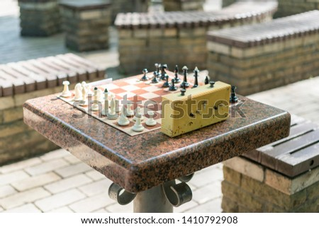 Chess board with pieces and clock on wooden desk In connection with the chess tournament. Chess tournament with chess clock on wooden table #1410792908