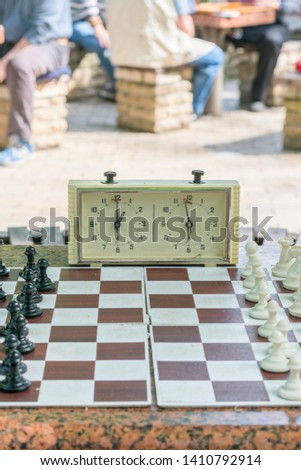 Chess board with pieces and clock on wooden desk In connection with the chess tournament. Chess tournament with chess clock on wooden table. vertical photo #1410792914