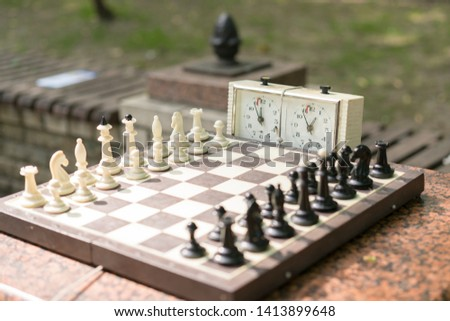 Chess board with pieces and clock on wooden desk In connection with the chess tournament. Chess tournament with chess clock on wooden table #1413899648