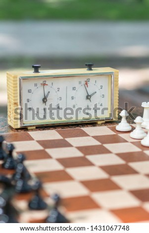 Chess board with pieces and clock on wooden desk In connection with the chess tournament. Chess tournament with chess clock on wooden table. vertical photo #1431067748