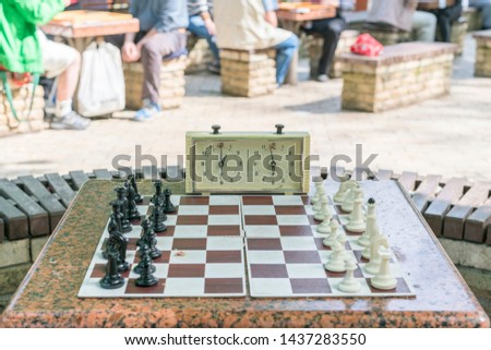 Chess board with pieces and clock on wooden desk In connection with the chess tournament. Chess tournament with chess clock on wooden table #1437283550