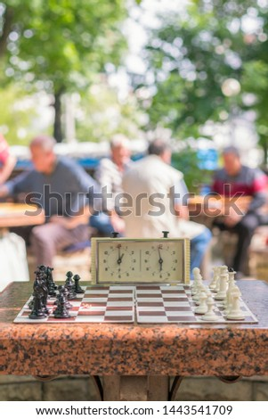 Chess board with pieces and clock on wooden desk In connection with the chess tournament. Chess tournament with chess clock on wooden table. vertical photo #1443541709
