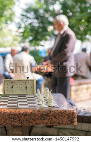 Chess board with pieces and clock on wooden desk In connection with the chess tournament. Chess tournament with chess clock on wooden table. vertical photo #1450147592