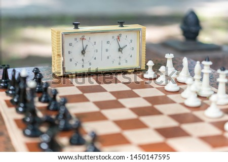 Chess board with pieces and clock on wooden desk In connection with the chess tournament. Chess tournament with chess clock on wooden table #1450147595