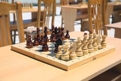 Chess board with yellow  and brown  figures . Yellow and brown photo with a picture of a chess Board pieces, Wooden pieces on a chess Board . How to play wooden chess game.