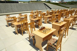 Chess board with yellow  and brown  figures . Yellow and brown photo with a picture of a chess Board pieces, Wooden pieces on a chess Board  and emtye table . How to play wooden chess game.