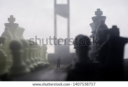 Chess concept of business and strategy ideas. Silhouette of a man standing in the middle of the road with giant chess figures and Guillotine. Artwork decoration. Selective focus #1407538757
