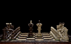 Chess faceoff of both kings on top of a chess board in front of a dark background surrounded by the queen, bishop, knight, rook and pawns