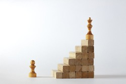 Chess figures on a toy wooden ladder - a chess pawn on the bottom and a chess queen on top, concept to symbolize achievement, growth and success.