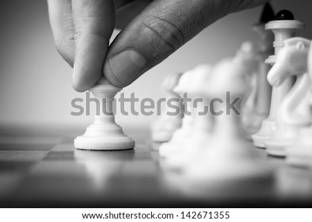 chess game, chess player makes a move the black pawn forward