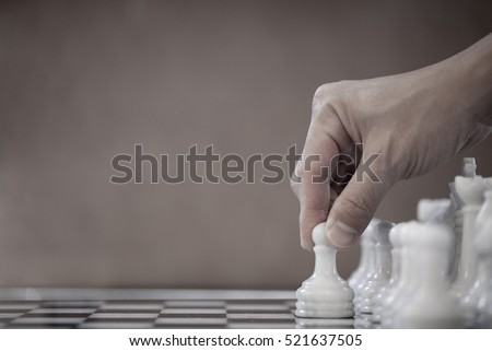 Chess game, chess player makes a move the white pawn one step forward. Chess pieces on the board. Man plays chess and makes the first move a pawn. Chessman playing chess, and showing the hand.