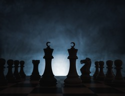 Chess game concept of challenge, ideas and competition. Chess figures isolated with dark background with fog and white light.