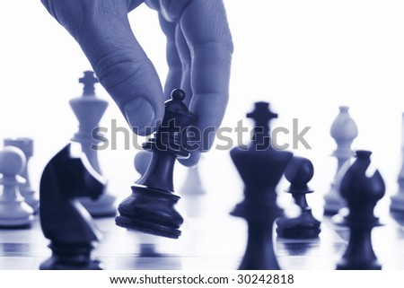 Chess game make your move blue tone close up of hand and chess pieces