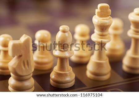 Chess game on wooden brown board.