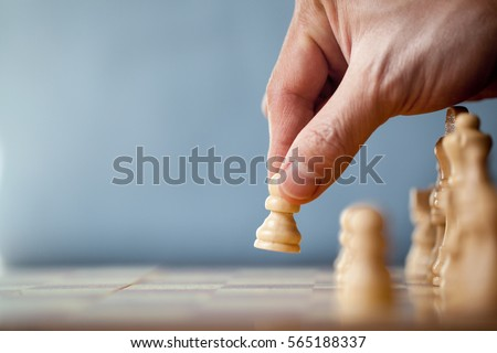 Chess game player makes a move the white pawn one step forward. Chess pieces on the board on blue background. Chessman playing chess and makes the first move a pawn, and showing the hand.