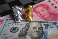 Chess game, two knights face to face on Chinese yuan and US dollar background. Trade way concept. Conflict between two big countries, USA and China concept. Copy space for text.