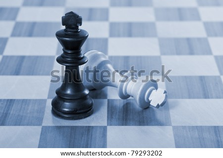 Chess game. White and black kings fight. Blue tone.