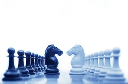 Chess horses facing each other for a standoff in cool tones