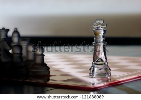 Chess King / Pieces - chess business concept - strategy, advertising, marketing, sales, stand out, competition, challenge, leadership, business skills, success. King in light, other pieces in shadow. - stock photo