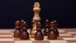 Chess, many against one, the concept of teamwork. Black pawns surrounded the white Queen