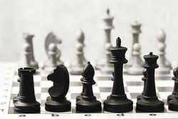 chess on a chessboard - black and white wooden chess pieces - black and white