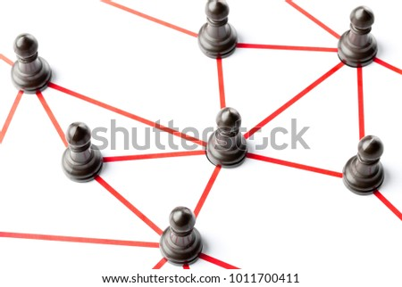 Chess pawn figures connected by red lines over white background - teamwork, connections or social network concept #1011700411