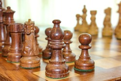 Chess photographed on a chessboard. Wood chess pieces on board game. Brown vintage Chess on blurred background.