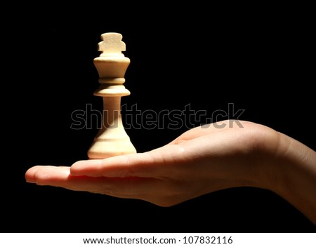 Chess piece in hand isolated on black