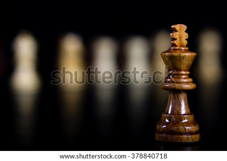Chess piece King in foreground with multiple with pieces in background #378840718