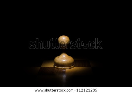 Chess piece pawn against a  black background close up