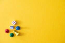 Chess pieces, game chips, Lotto barrels, draughts and playing cubes are laid on a yellow background: entertainment, games at home for the whole family, the concept of table games