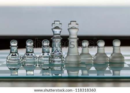 Chess pieces, king, pawns on chess board - business concept series for strategy, opposition, business challenge, competition, amalgamate, merge or takeover?  - stock photo