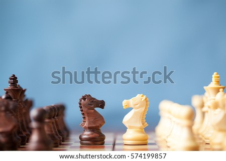 Chess pieces knights facing each other for a standoff on chessboard with blue background. Chess knights confronting each other. Chess knights head to head.