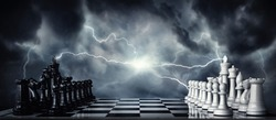 Chess pieces on a chessboard against the background of a dark stormy sky. Game of chess as symbol of strategy, leadership and business victories. Concept on the topic of struggle, clashes in politics.