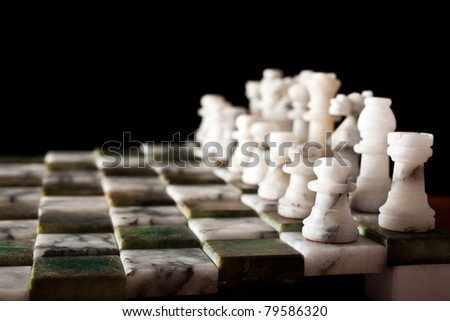 Chess pieces on a marble board - stock photo