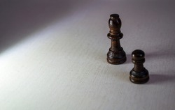 Chess pieces on a white background, people like pawns.