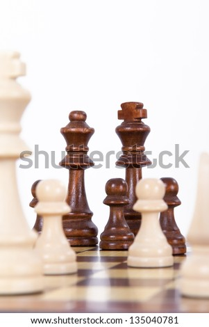 Chess pieces on board with depth of field, isolated on white background.
