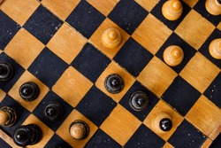 Chess Pieces on old Vintage Wooden used Chess Board, Game of Checkers, flat lay
