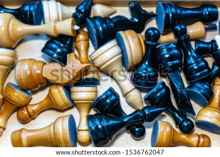 chess pieces scattered around, top down view. Randomly placed black and light colour chess pieces - conceptual image around the themes of organization, chaos, randomness, ceasefire, pause, teamwork #1536762047