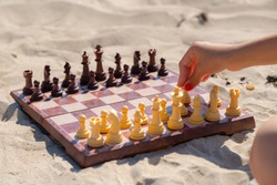Chess play on the board at the beach. Chessboard on the sand on a sunny day.