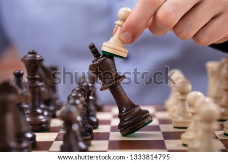 Chess Player Makes A Move To Defeat King Piece Stock photo ©