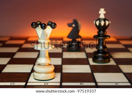 Chess (queen, king and a horse) on a chess board. An art dark background.