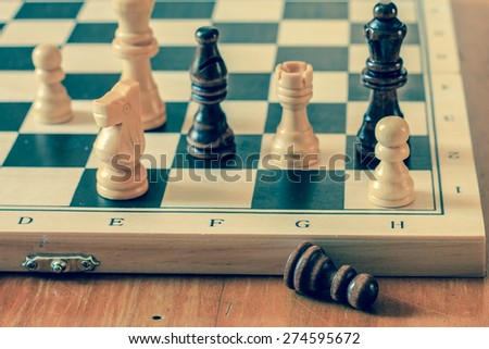 Chess set and chess pawn on wooden table, game and strategy concept, vintage photography.