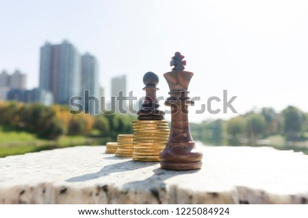 Chess standing on gold coins, victory and accumulation of wealth